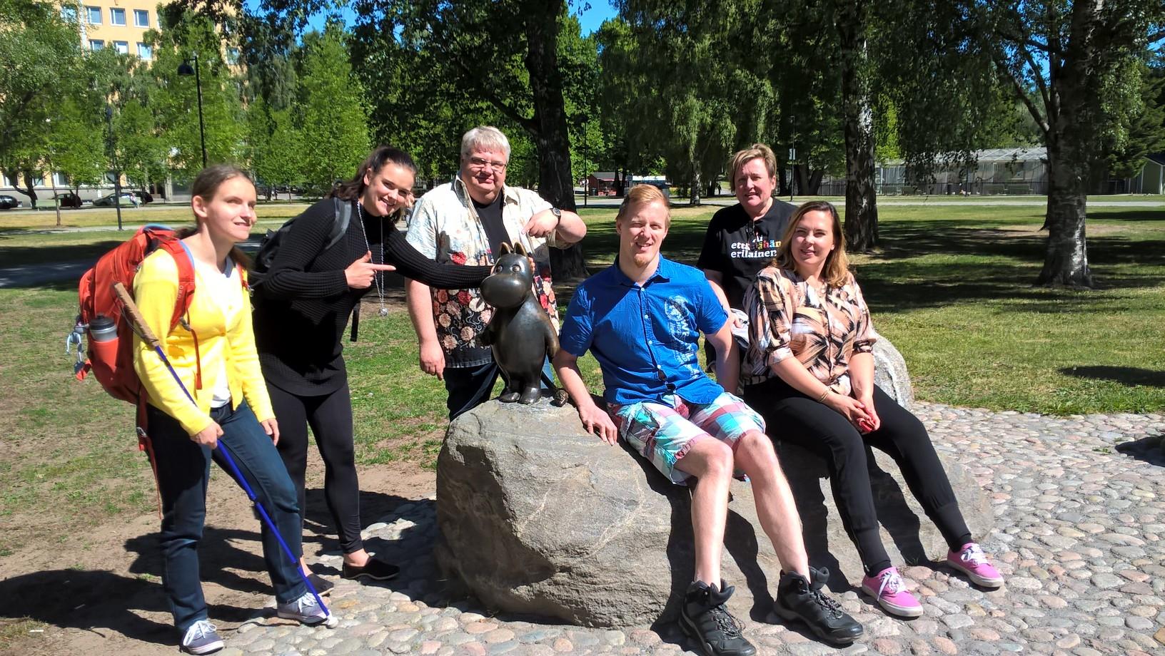 Kuva Sorsapuistosta Tampere-talon läheltä. Kuvassa muumipeikko-patsaan ympärillä: Ronja Oja, Mia Purho, Markku Vellas, Osku Timonen, Jaana Teräväinen, Veera Virta.