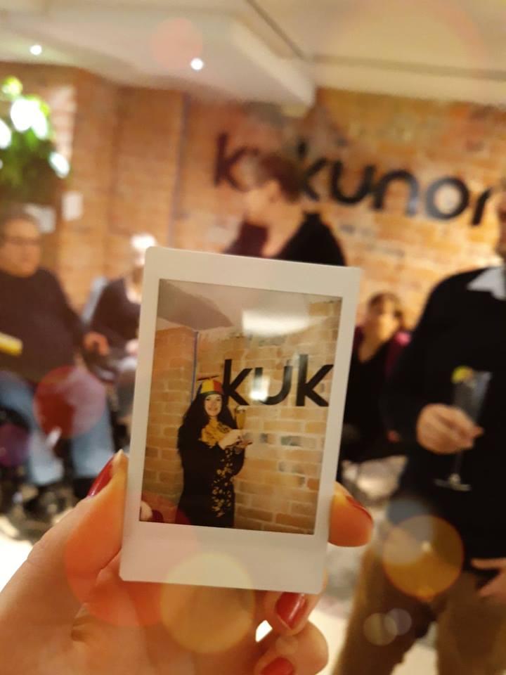 Kuvassa iloinen henkilö propellihatussa, taustalla seinällä lukee Kukunori