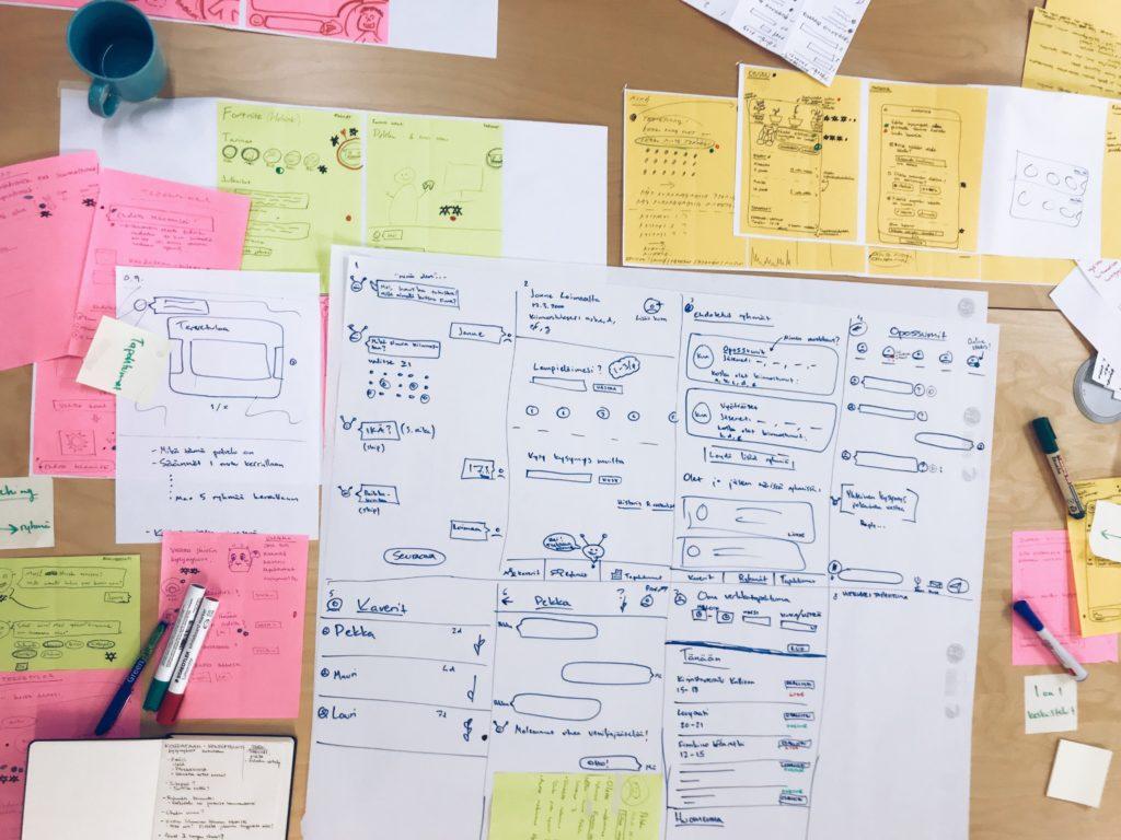 Pöydällä paljon papereita, joissa muistiinpanoja tekstinä ja piirroksina.